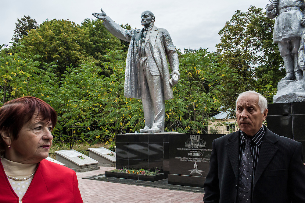SEMYONOVKA, UKRAINE - SEPTEMBER 13, 2015: Tatyana I. Pus, 68, left, and Ivan M. Papchenko, 67, the secretary of the local Communist party, near a reconstituted statue of Vladimir I. Lenin in Semyonovka, Ukraine. The statue, which was taken down from the town square in the immediate aftermath of the collapse of the government of President Viktor Yanukovych in February 2014, was erected again in a new, more discreet, location in a park two months later based in part by a petition to the city council submitted by the local Communist party. A new decommunization law has stirred criticism as being a diversion from more pressing issues of war and the economy. CREDIT: Brendan Hoffman for The New York Times