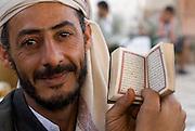 Man holding a small copy of the Koran. Market in Sanaa.