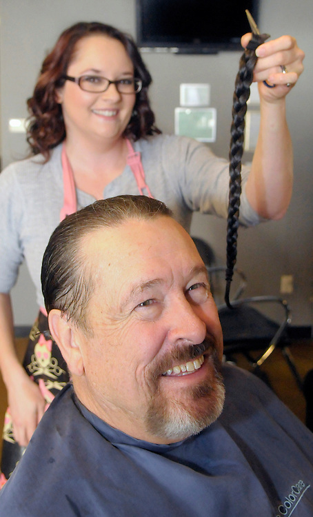 gbs121213f/ASEC -- Audrey Morelock holds the braided long hair she cut off of her father, John Morelock, at the Hair Addict salon on Thursday, December 12, 2013. The braided locks with be donated to Pantene Beautiful Lengths which gives free wigs to adult cancer victims.(Greg Sorber/Albuquerque Journal)