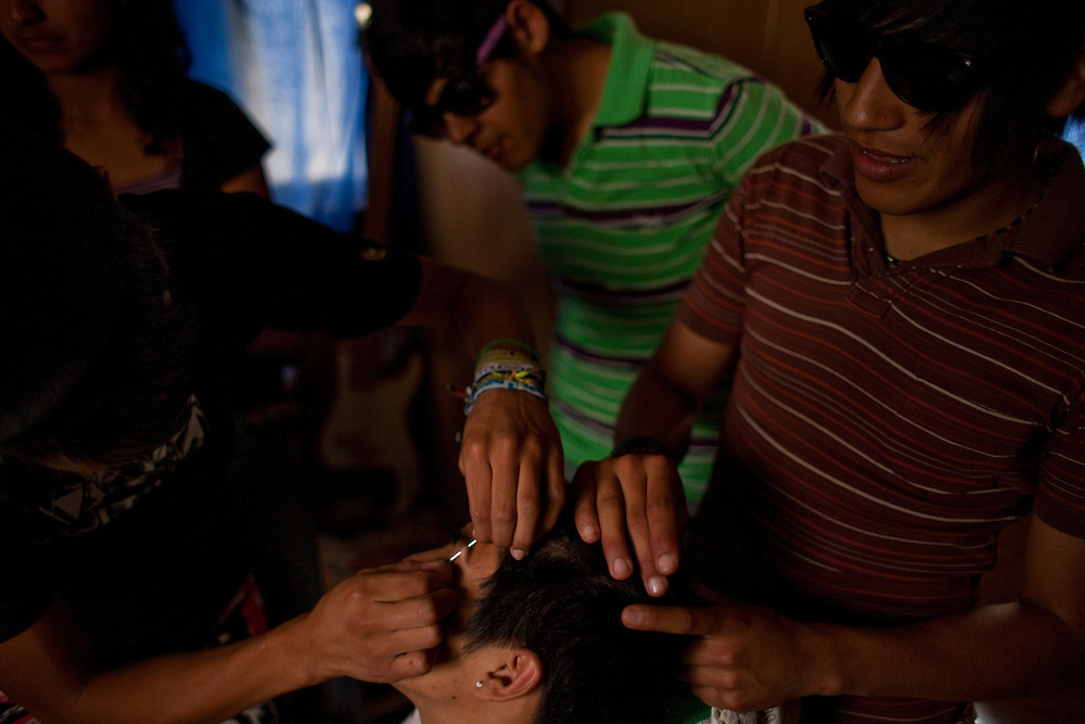 Gustavo Martinez, 19, gets a piercing from his friend at their house in the Diaz Ordaz colonia in Ciudad Juarez, Chihuahua Mexico on April 28, 2010. ..
