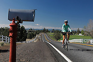 Bicycle rider on Country Road, mail box, Bend, Central Oregon, Oregon, USA