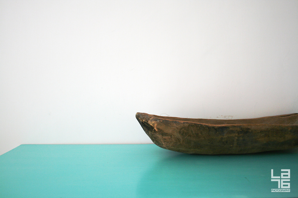 Wooden bowl and a turquoise table.<br /> Photo shooting took place in a modern, minimalistically decorated beachfront home in exotic small town of Los Barriles, Baja California Sur, Mexico. <br /> Home decoration is comprised of different color selections, each used with careful combination of details and accompanying furniture, plants and other decorative elements. Prevailing colors are white, red and striking turquoise blue.<br /> Here we are showing photographs from 2 parts of this home; guest bedroom and inner patio, where magnificent red wall with agavas welcomes you upon arrival. And if you are lucky enough to get an invite to stay in the house over night, you will enjoy a beautiful bedroom, with minimal decoration, but very attractive, relaxed and Mexican, but in a contemporary way.