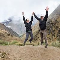 Peru, Hikers leap to celebrate 13,800' summit of Dead Woman's Pass along Inca Trail to Machu Picchu along Urubamba River