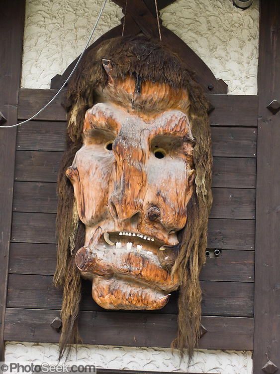 """A carved wood troll or ogre head with teeth decorates a wall in Zermatt. The famous mountaineering and ski resort of Zermatt lies at 1620 meters or 5310 feet elevation at the head of Mattertal (Matter Valley) in Valais canton, Switzerland, the Pennine Alps, Europe. Zermatt bars combustion-engine cars to help preserve small village atmosphere and prevent air pollution. The German word matten means """"alpine meadows."""" Most visitors reach Zermatt by cog railway train from the nearby town of Täsch (Zermatt shuttle). Trains also depart for Zermatt from farther down the valley at Visp and Brig on the main Swiss rail network. Hike the High Route (Chamonix-Zermatt Haute Route) for exceptional mountain scenery."""