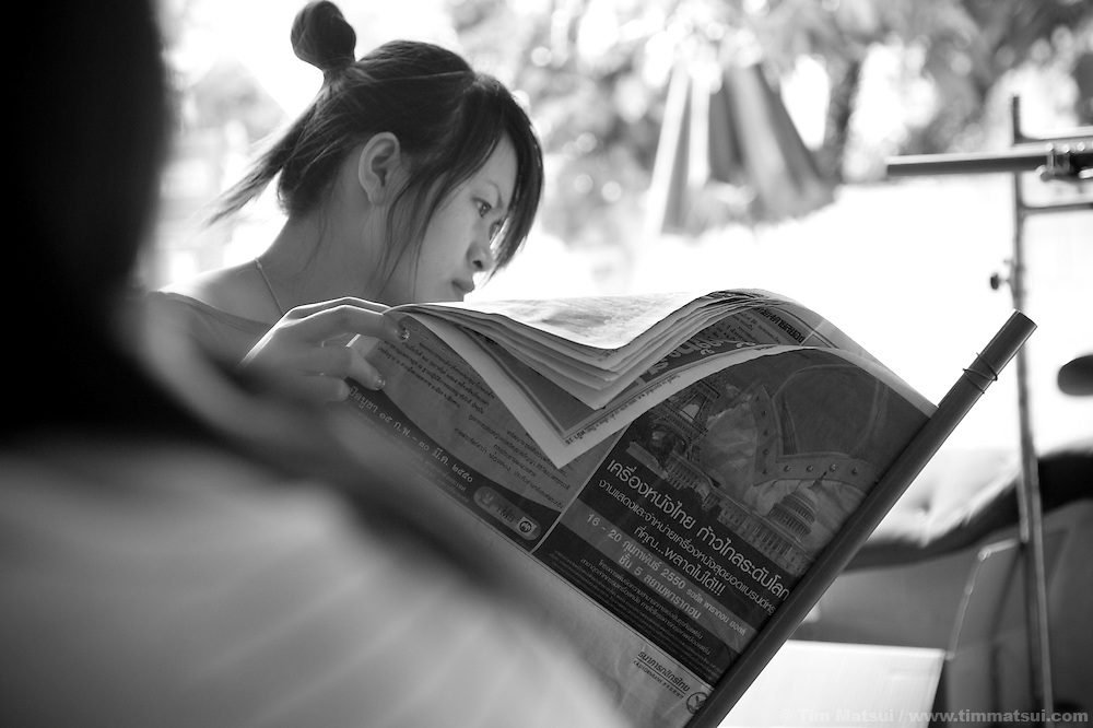 "ID: Mong reads the paper. >> Women at the Chiang Mai office of the Empower Foundation in northern Thailand, which serves as a drop-in center offering computer and informal English training, health education, counseling and other support to sex workers. Founded in 1985 the organization has five centers from Phuket to Mai Sai and advocates for recognition, equality, and basic human rights for sex workers in Thai society where sex work is common, visible, and yet illegal..>>.Empower Chiang Mai opened the ""Can-Do"" bar which offers fair working conditions to sex workers by complying with all Thai Labor Laws and the recommended occupational health and safety standards..>>.Empower, which works with women over 18 years-old and is a vocal opponent of human trafficking, sexual or labor exploitation of any person,  is also campaigning to change the methods of anti-human trafficking groups. Empower states ""the focus on trafficking in persons has meant many groups with little or no experience on the issues of migration, labor, sex work or women's rights have been created to take advantage of the large sums of money available to support anti-trafficking activities."".>>.Recommendations by sex workers, many who were Burmese, some who had been trafficked, and all who acknowledged enlisting an agent to migrate illegally into Thailand, stated among other things that ""The primary goal of prosecuting traffickers must be altered to a primary goal of assisting trafficked women and children...if trafficked women and children...are continually rescued and assisted, the use of trafficked women and children will become unprofitable...we are willing to work our illegal status leaves us with no recourse against exploitation by agents or employers...Anti-trafficking groups must work toward improving the human rights situation...Anti-trafficking dialogue and groups have yet to consider us as anti-trafficking workers and human rights defenders...The latest stance from the USA government calling us"