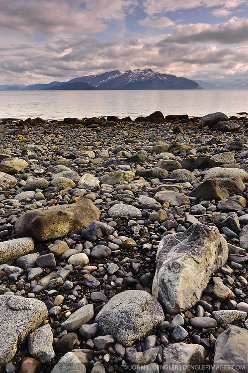 Rocks are exposed at low tide on a beach at Tlingit Point in Glacier Bay National Park and Preserve in southeast Alaska. In the background is Drake Island. Beyond Drake Island is Marble Mountain.