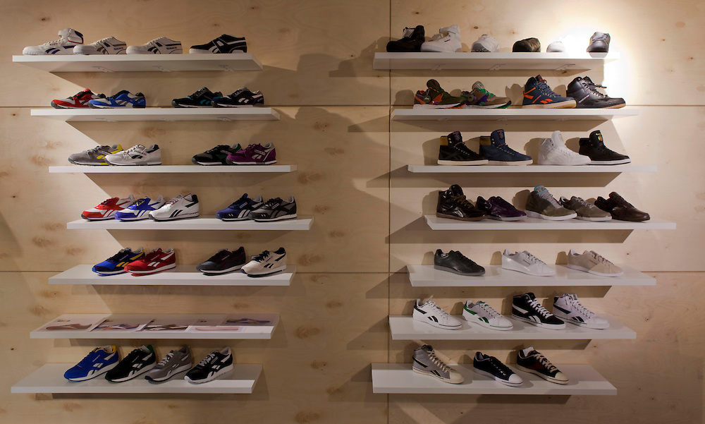 A wall display of trainers on shelves at a reebok showroom