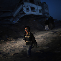 A young Palestinian boy runs in front of a destroyed house at Jabalia's Ezbet Abed Rabbo district in the northern Gaza Strip on January 26, 2009. An ongoing Saudi campaign to raise aid for the battered Gaza Strip has so far raised 59.8 million dollars, including 10.7 million dollar from King Abdullah bin Abdul Aziz and his crown prince.