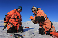 Marine chemists Agneta Fransson (Norwegian Polar Institute) and Melissa Chierici (Institute of Marine Research) process ice core atop frozen fjord; Kongsfjord, Svalbard, Norway.