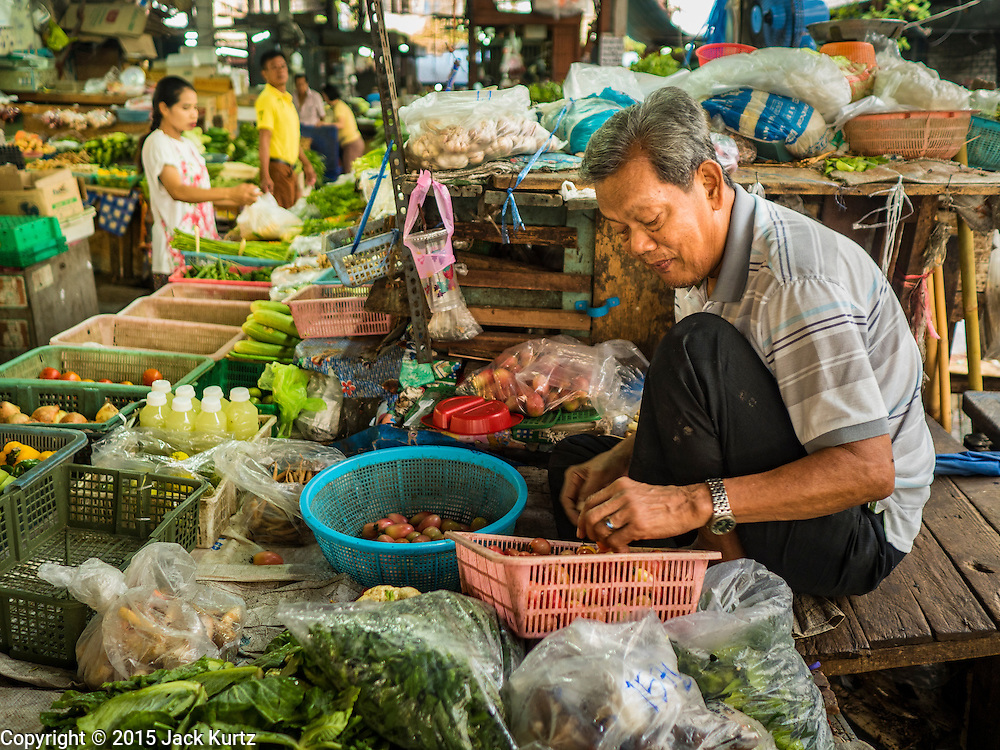 14 DECEMBER 2015 - BANGKOK, THAILAND:  A vendor sorts vegetables he sells in Bang Chak Market. The market closes permanently on Dec 31, 2015. The Bang Chak Market serves the community around Sois 91-97 on Sukhumvit Road in the Bangkok suburbs. About half of the market has been torn down. Bangkok city authorities put up notices in late November that the market would be closed by January 1, 2016 and redevelopment would start shortly after that. Market vendors said condominiums are being built on the land.      PHOTO BY JACK KURTZ