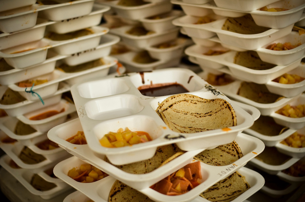 Prisoners' dinner consisting of tortillas, black bean mash, and squares of lunchmeat mixed with chunks of canned pineapple at Izalco men's prison for incarcerated members of the Mara 18 gang, in El Salvador.