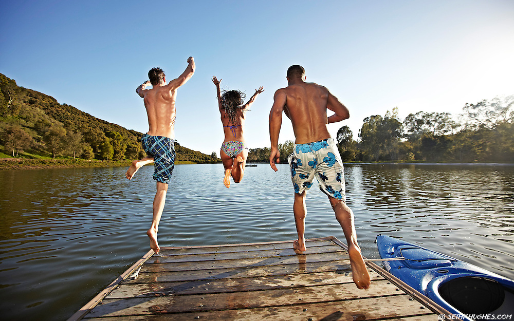Summer is in full swing as friends run and jump off the end of a lakeside dock.