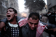 Protester dazed by tear gas is helped out of Mohamed Mahmoud street near Tahrir Square during stand off and clashes with riot police on November 22, 2011 in Cairo, Egypt.