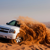 United Arab Emirates, Dubai, Four wheel drive truck sends up spray of sand while driving at dune bashing site in Al Aweer Desert