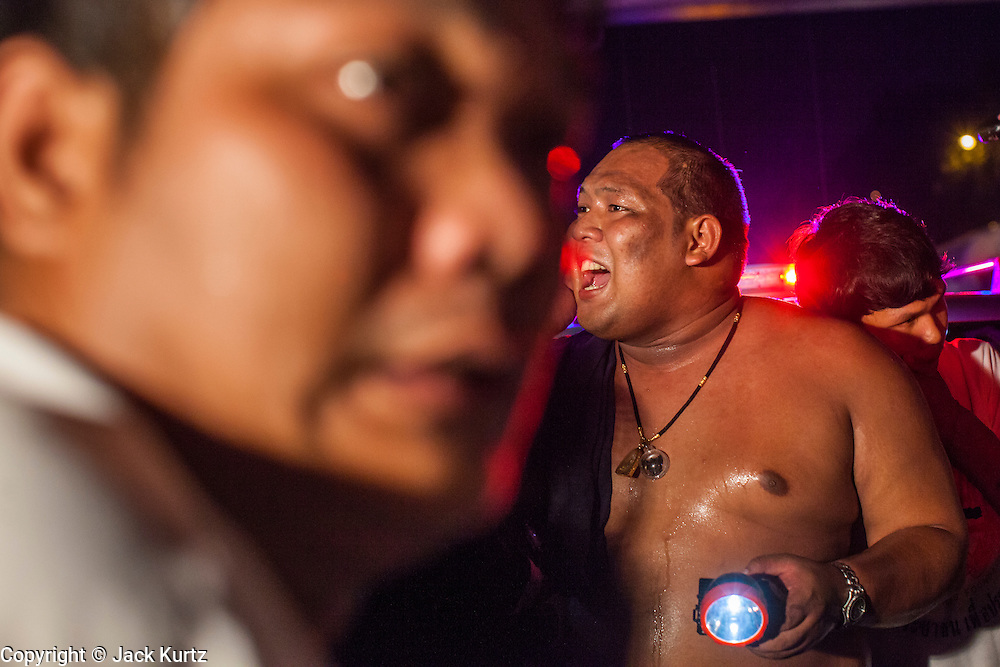 """10 NOVEMBER 2012 - BANGKOK, THAILAND:  A man shouts instructions into the crowd while holding a flashlight for emergency medics from the Ruamkatanya Foundation at the scene of a fatal accident involving a child in Bangkok. The Ruamkatanyu Foundation was started more than 60 years ago as a charitable organisation that collected the dead and transported them to the nearest facility. Crews sometimes found that the person they had been called to collect wasn't dead, and they were called upon to provide emergency medical care. That's how the foundation medical and rescue service was started. The foundation has 7,000 volunteers nationwide and along with the larger Poh Teck Tung Foundation, is one of the two largest rescue services in the country. The volunteer crews were once dubbed Bangkok's """"Body Snatchers"""" but they do much more than that now.    PHOTO BY JACK KURTZ"""