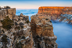 In what is known as a temperature inversion, clouds fill the Grand Canyon when cold air below the rim is trapped by warmer air above.