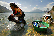 Maria Gomez, 16, orange top, and her friend Isabel Hernandez, 17, perform their daily task of washing their clothes on the shores of Lake Atitlan in Santa Caterina Palopo, Guatemala.