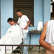 "To make money that he plans on spending to gain passage to the US, where his sister lives, this man (who prefers not to give his name) gives haircuts on his front porch. Cubans are assigned ""careers"" by government officials, so many have side-jobs which provide extra income under the table. ltqmb CUBA: BARBER"