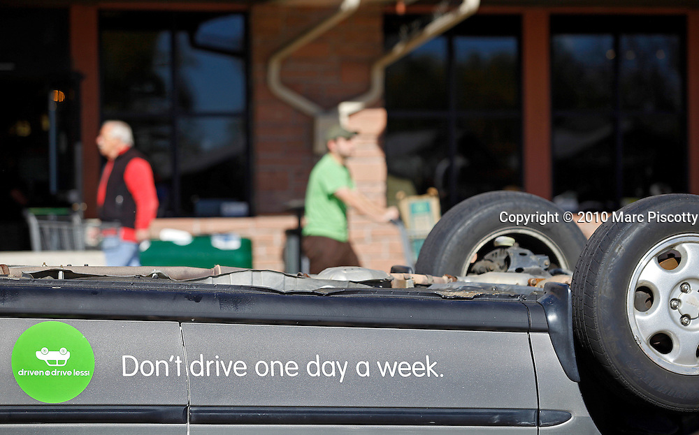 SHOT 11/6/10 12:37:16 PM - Members of Driven to Drive Less display a car turned upside down and offer free bike tunes and maintenance in front of the Whole Foods grocery store in Boulder, Co. on Saturday November 7, 2010. Driven to Drive Less is a program being undertaken by the city of Boulder, Co. that encourages participants to stimulate long term travel behavior change and to creatively demonstrate to the general public the ability of Boulder residents to live car free or car lite. Participants receive benefits and discounts at local stores for pledging to give up driving their vehicle one day a week. (Photo by Marc Piscotty / © 2010)