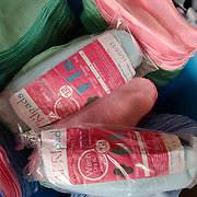 Sanitary pads awaiting lining and sewing are seen with packs of the finished product at the Afripads factory in the village of Kitengeesa in the Central Region of Uganda on 30 July 2014. Started by volunteers in 2009, Afripads manufactures reusable fibre sanitary pads made locally by community residents. Beginning with a single employee, the company now employs roughly 100 women and produces approximately 700 kits (consisting of pads, holders and a bag) each week. At USh 12,000 to 15,0000 (£2.75 to £3.40) for a kit that lasts approximately one year, Afripads offer a significant saving over disposables which may cost in excess of USh 42,000 (£9.60) over the course of a year. And for the many girls and women who cannot afford disposables, they offer an affordable and more hygienic alternative to rags, cotton wool or toilet paper, all of which are frequently used. At schools where Afripads have been distributed, teachers report that absenteeism has dropped sharply as girls who previously did not have access to proper sanitary pads now no longer stay home when they have their periods.