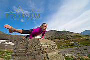 woman doing yoga hand balance on rock dramatic mountains