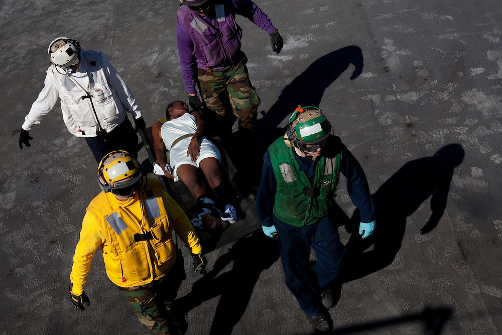 A Haitian earthquake victim is carried on the flight deck after arriving by helicopter on board the USNS Comfort, a U.S. Naval hospital ship, on January 21, 2010 in Port-au-Prince, Haiti. The Comfort deployed from Baltimore with 550 medical personnel on board to treat victims of Haiti's recent earthquake, and arrived on January 20.