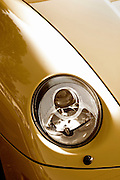 Image detail of modern headlight on yellow sports car fender, Porsche 993