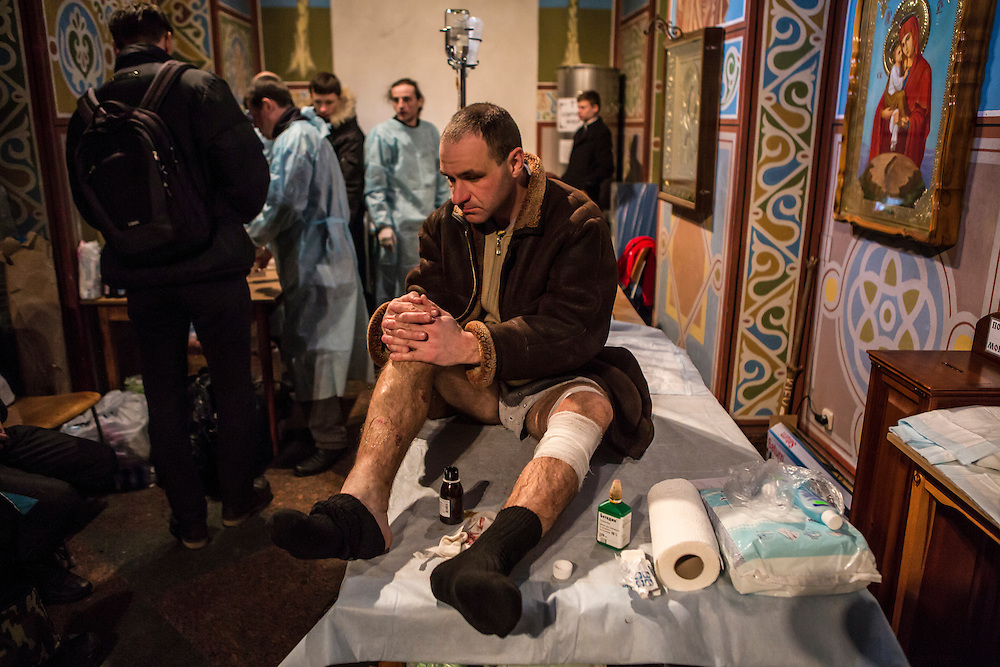 KIEV, UKRAINE - FEBRUARY 19: An injured anti-government protester awaits treatment at the Mikhailovsky Monastery, which has been converted into a makeshift hospital, on February 19, 2014 in Kiev, Ukraine. After several weeks of calm, violence has again flared between police and anti-government protesters, who are calling for the ouster of President Viktor Yanukovych over corruption and an abandoned trade agreement with the European Union. (Photo by Brendan Hoffman/Getty Images) *** Local Caption ***