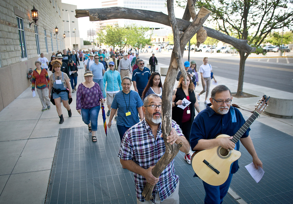 mkb041217a/metro/Marla Brose --  Robert Salcido, front left, and Larry Gallegos, front right, lead a procession around the Bernalillo County Courthouse during Friday's Urban Way of the Cross pilgrimage around Downtown Albuquerque, April 14, 2017. People from various churches and organizations stopped at different locations for the nine stations to reflect on Good Friday. (Marla Brose/Albuquerque Journal)