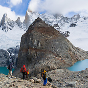"""On the border between Argentina and Chile, Mount Fitz Roy rises into clouds 2500 meters (8200 feet) above Lago Sucia (left) in Los Glaciares National Park, in the southern Andes mountains, Patagonia, Argentina, South America. Hike to the glacial cirque of Laguna de los Tres (right) from El Chaltén village, which was built in 1985 by Argentina to help secure the disputed border with Chile. The frontier tourist town of El Chaltén is 220 km (3 hours drive) north of the larger town of El Calafate. In 1877, explorer Perito Moreno named ?Cerro Fitz Roy? for Robert FitzRoy (with no space before the capital R) who, as captain of the HMS Beagle, had travelled up the Santa Cruz River in 1834 and charted much of the Patagonian coast. First climbed in 1952 by French alpinists Lionel Terray and Guido Magnone, Mount Fitz Roy (3405 meters or 11,170 feet elevation) has fickle, windy weather and is one of the world's most challenging technical ascents. It is also called Cerro Chaltén, Cerro Fitz Roy, and Monte Fitz Roy (with a space before the R). Chaltén comes from a Tehuelche (Aonikenk) word meaning """"smoking mountain"""" (explained by frequent orographic clouds). Cerro is a Spanish word meaning hill. The foot of South America is known as Patagonia, a name derived from coastal giants, Patagão or Patagoni, who were reported by Magellan's 1520s voyage circumnavigating the world and were actually Tehuelche native people who averaged 25 cm (or 10 inches) taller than the Spaniards. Mount Fitz Roy is the basis for the Patagonia company's clothing logo, after Yvon Chouinard's ascent and subsequent film in 1968."""