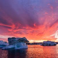 Canada, Nunavut, Territory, Setting midnight sun lights clouds above melting iceberg in Hurd Channel near Vansittart Island's Cape Shackleton just south of Arctic Circle