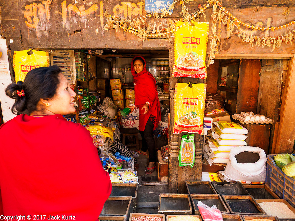 03 MARCH 2017 - BHAKTAPUR, NEPAL: A Nepali woman shops in Bhaktapur. IN some ways, life has returned to normal in Bhaktapur but evidence of the 2015 earthquake is everywhere. Bhaktapur, a popular tourist destination and one of the most historic cities in Nepal was one of the hardest hit cities in the earthquake. Recovery seems to have barely begun nearly two years after the earthquake of 25 April 2015 that devastated Nepal. In some villages in the Kathmandu valley workers are working by hand to remove ruble and dig out destroyed buildings. About 9,000 people were killed and another 22,000 injured by the earthquake. The epicenter of the earthquake was east of the Gorka district.      PHOTO BY JACK KURTZ