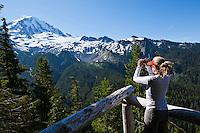A woman taking a picture on the Northwest side of Mount Rainier, Mount Rainier National Park, Washington, USA.