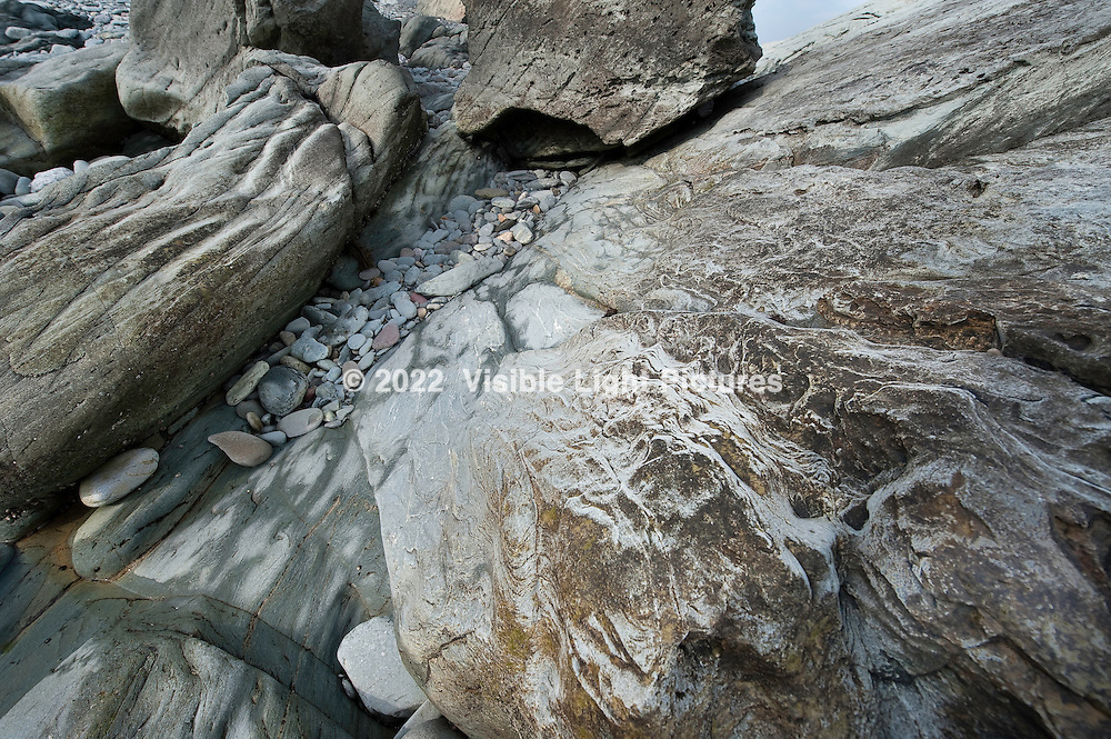 Rocks and stones worn smooth on the seashore. Rocky beach along the Sachuest Point National Wildlife Refuge