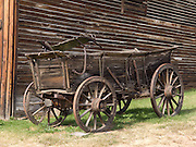 """A wagon with iron-bound wooden wheels stands outside a late 1800s livery stable preserved at the outdoor history museum of Nevada City, Montana, USA. Nevada City was a booming placer gold mining camp from 1863-1876, but quickly declined into a virtual ghost town. This fascinating town inspires you to imagination what life must have been like in early Montana when gold was discovered at nearby Alder Gulch. More than 90 buildings from across Montana have been gathered for preservation at Nevada City, mostly owned by the people of the State of Montana, and managed by the Montana Heritage Commission. In 2001, the excellent PBS television series """"Frontier House"""" used one of the buildings and its furnishings to train families in re-creating pioneer life. A miner's court trial and hanging of George Ives in the main street of Nevada City was the catalyst for forming the Vigilantes, a group of citizens famous for taking justice into their own hands in 1863-1864. Directions: go 27 miles southeast of Twin Bridges, Montana on Highway 287."""