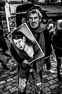 "March 2015. Paris. An artist holding a girl's portrait in Montmartre. They do a ""souvenir"" portraits fort the big amount of  tourists who visit each day this famous district of Paris."