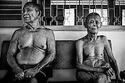 Two elderly male patients sit quietly at Ben San leprosy center, near Saigon, Vietnam.