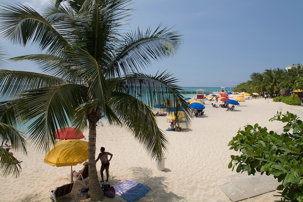 Jamaica,  Montego Bay, Tourists and palm tree along white sand beach at Doctor's Cave