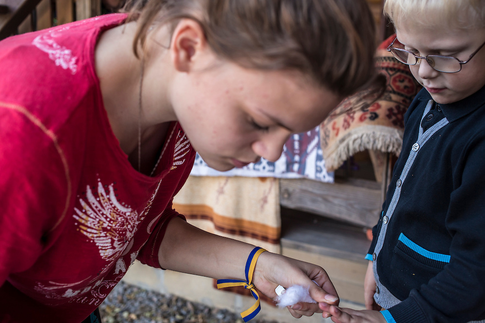 A woman with a pro-Ukraine ribbon tied around her wrist cleans a boy's hands on Tuesday, October 14, 2014 in Berdyansk, Ukraine. They are part of a group of internally displaced people who fled the besieged city of Donetsk and are now living in a small seaside resort. Photo by Brendan Hoffman, Freelance