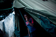 A resident stands in her tent in a Red Cross-run camp in the Mathare section of Nairobi, May 25, 2008. More than 300,000 Kenyans were left homeless after President Mwai Kibaki's disputed re-election in December triggered ethnic clashes, killings and looting. Some aid workers estimate that half of them have returned home, but many are still too afraid or don't have enough resources to do so despite reassurances from the power-sharing government.
