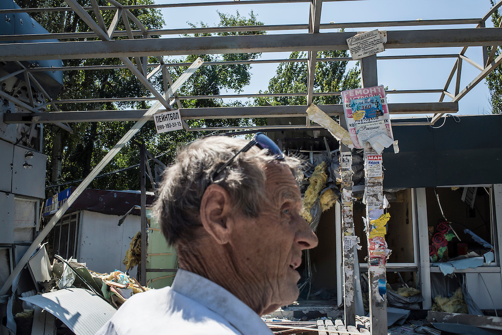 A man surveys the damage from shelling of shops in the Oktyabrskaya neighborhood on Sunday, July 27, 2014 in Donetsk, Ukraine.