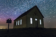 The old Liberty Schoolhouse at Majorville, Alberta, with some fun with lighting the interior. This schoolhouse was built in 1909, as the classic one room school on the prairies. This is a stack of 12 exposures for the star trails with Lighten Blend mode, plus 5 exposures for the ground with Mean Combine stack mode to smooth noise in the dark ground. Each was 20 seconds at f/2.8 with the 16-35mm lens and Canon 60Da at ISO 3200.