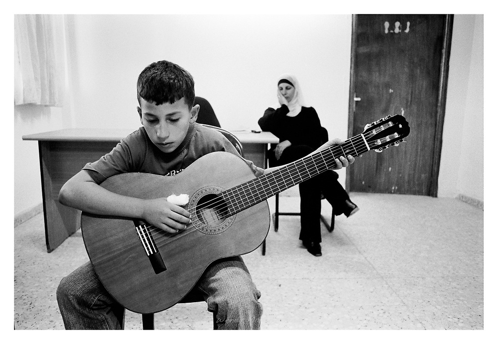 A young boy during a guitar lesson by the Al-Kamandjati school in Qalandiya refugee camp. The school sends it teachers on the road to children that are not able to reach the school due to checkpoints, etc. Qalandiya, Palestine, 2007