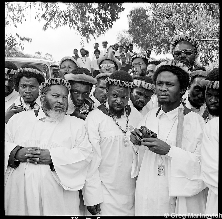 Church members sceptically check out a man claiming to have just been healed from a long-standing paralysis, at the church headquarters near KwaMashu, KwaZulu Natal, January 1998. The founder Isaiah Shembe is seen as a spiritual descendent of Moses and Jesus, and th church embraces traditional Zulu values and customs. Photo Greg Marinovich