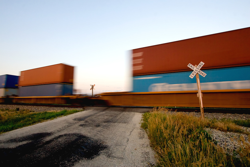A southbound train of international containers zooms by a rural crossing south of Chicago, IL.