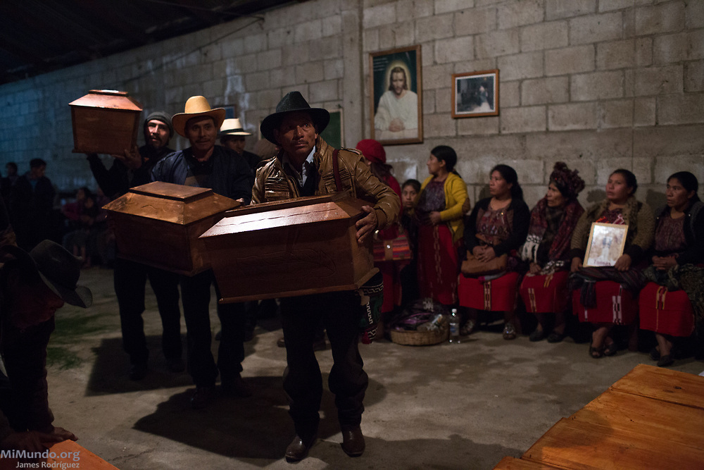 Ixil Mayan people from Acul, Nebaj, gather as the human remains of 36 war victims are waked by surviving family members before a proper burial. Most of the victims, exhumed from mass graves in Xe'xuxcap, near Acul, starved in the mountainside while fleeing State-led repression in 1982. Most of the remains, exhumed by members of the Forensic Anthropology Foundation of Guatemala (FAFG) in 2013, were identified using DNA analysis and buried 35 years after their death. Acul, Nebaj, Quiché, Guatemala. February 2, 2017.
