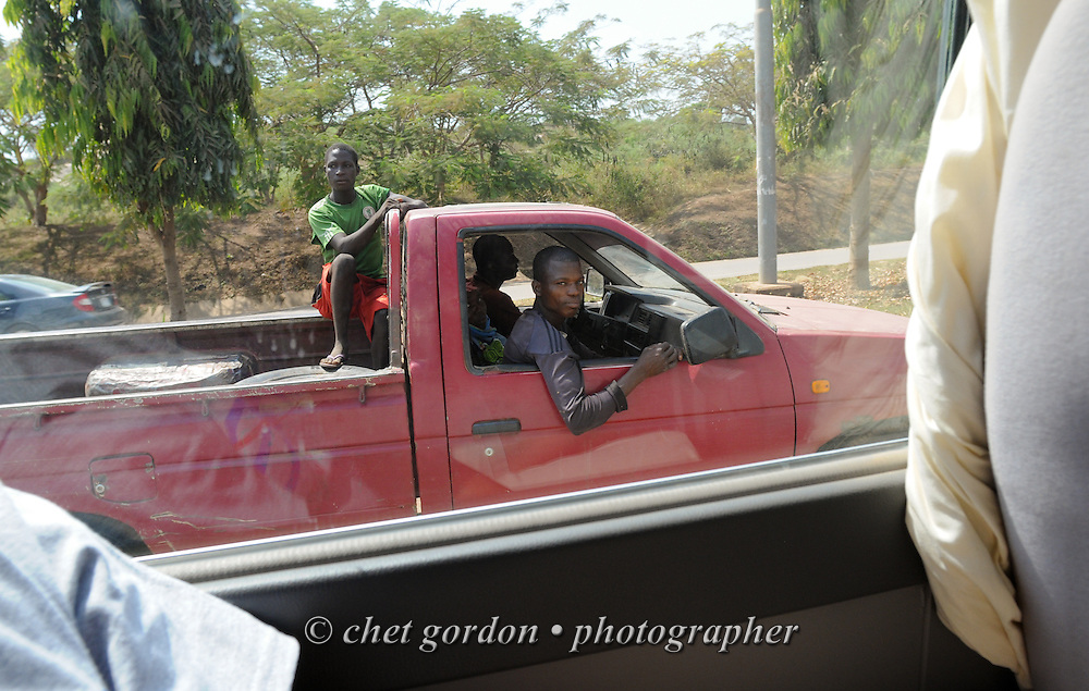 Young Nigerian men in a pickup truck in midday traffic in Abuja, Nigeria on Sunday, December 2, 2012.