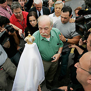 Bob Schindler (C) looks at a statue of the Virgin Mary presented to him by supporters of his daughter Terri Schiavo outside  the Woodside Hospice on March 23, 2005 in Pinellas Park, Fla. Behind left is his daughter Suzanne Vitadamo. Photo by Scott Audette/Reuters