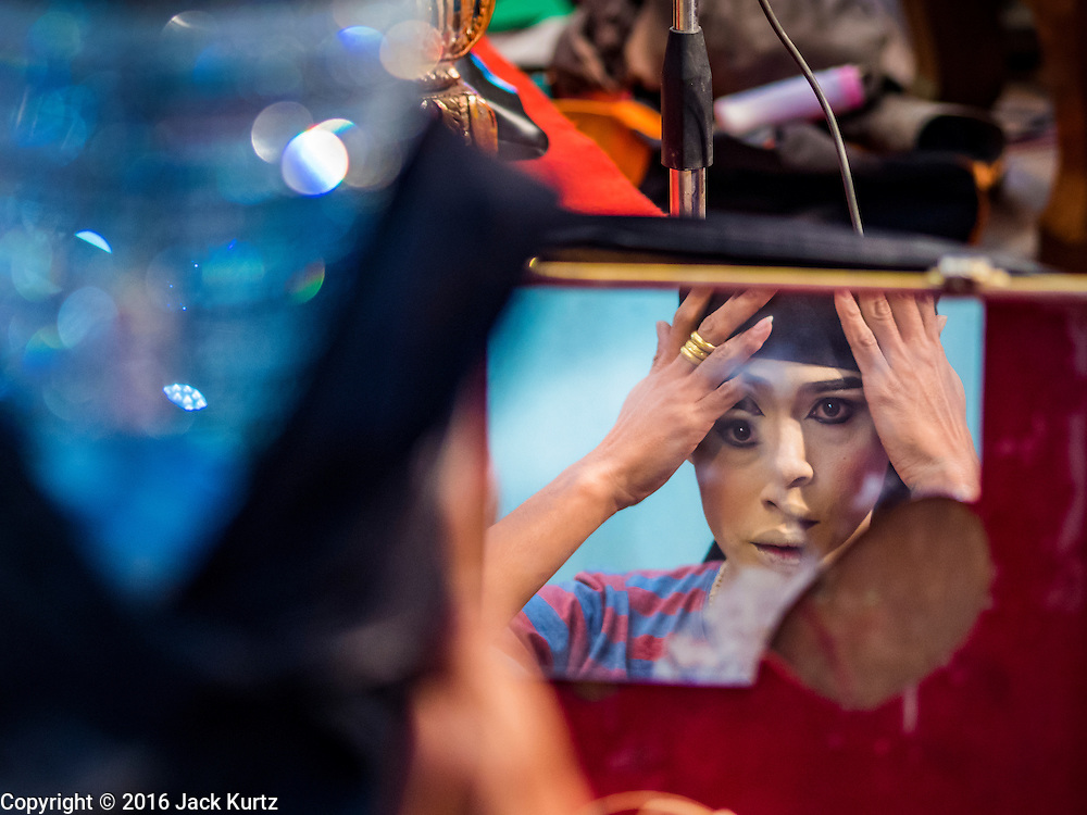 "30 JANUARY 2016 - NONTHABURI, NONTHABURI, THAILAND: A performer looks into a broken mirror while gets ready for a ""likay"" show at Wat Bua Khwan in Nonthaburi, north of Bangkok. Likay is a form of popular folk theatre that includes exposition, singing and dancing in Thailand. It uses a combination of extravagant costumes and minimally equipped stages. Intentionally vague storylines means performances rely on actors' skills of improvisation. Like better the known Chinese Opera, which it resembles, Likay is performed mostly at temple fairs and privately sponsored events, especially in rural areas. Likay operas are televised and there is a market for bootleg likay videos and live performance of likay is becoming more rare.     PHOTO BY JACK KURTZ"