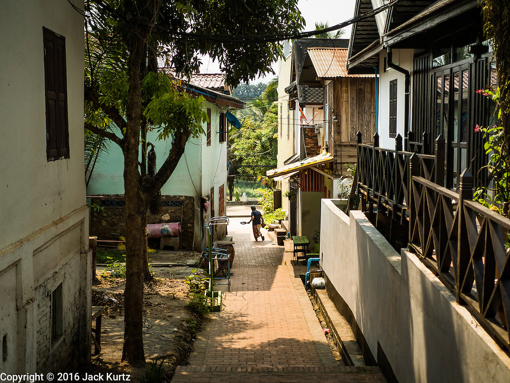 "13 MARCH 2016 - LUANG PRABANG, LAOS: A woman crosses a restored alley in a residential section of Luang Prabang. Luang Prabang was named a UNESCO World Heritage Site in 1995. The move saved the city's colonial architecture but the explosion of mass tourism has taken a toll on the city's soul. According to one recent study, a small plot of land that sold for $8,000 three years ago now goes for $120,000. Many longtime residents are selling their homes and moving to small developments around the city. The old homes are then converted to guesthouses, restaurants and spas. The city is famous for the morning ""tak bat,"" or monks' morning alms rounds. Every morning hundreds of Buddhist monks come out before dawn and walk in a silent procession through the city accepting alms from residents. Now, most of the people presenting alms to the monks are tourists, since so many Lao people have moved outside of the city center. About 50,000 people are thought to live in the Luang Prabang area, the city received more than 530,000 tourists in 2014.    PHOTO BY JACK KURTZ"